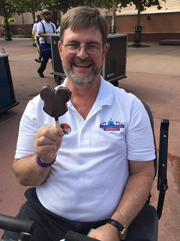 Dad eating a Mickey Bar, one of his favorite sweet treats in the Magic Kingdom