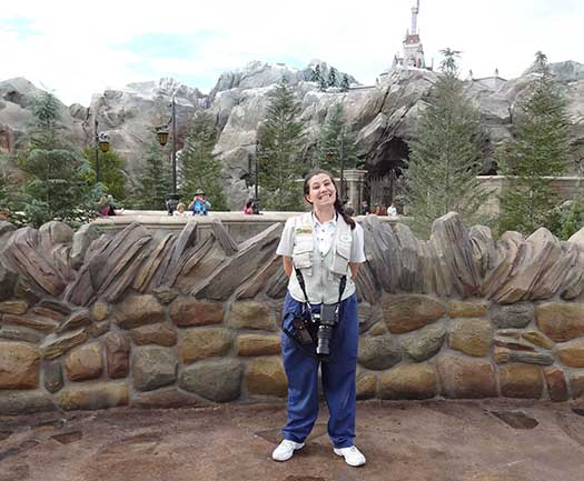 A PhotoPass photographer in front of Be Our Guest